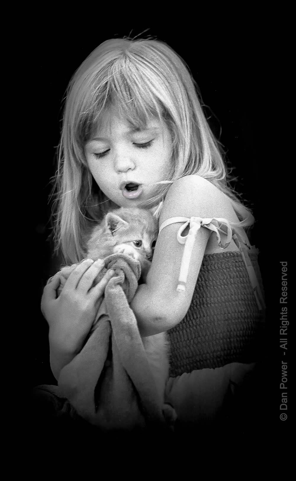 Young girl with kitten, black and white