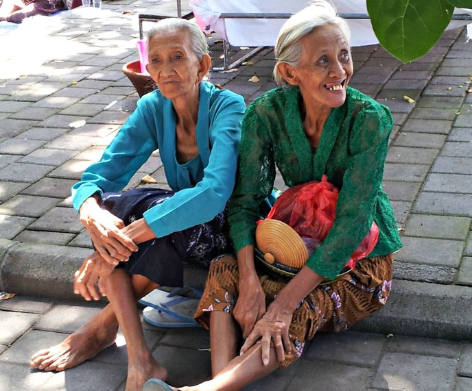 Two Balinese ladies sitting on the pavement watching the preparations for a cremation