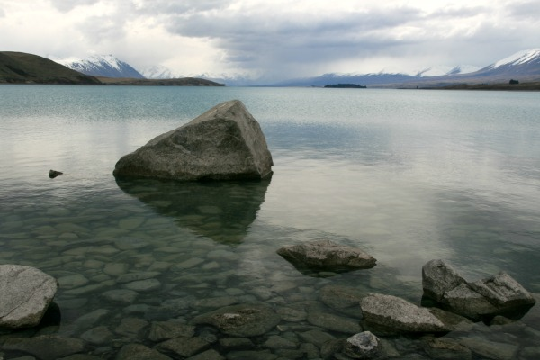 Large Rock in a Lake with Snowcapped Mountains.  Calming view for those coping with dementia