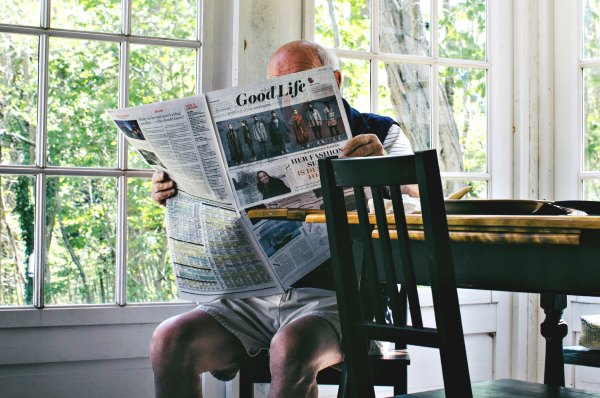 Grandfather sitting on chair reading newspaper entitled Good Life.  Photo by Sam Wheeler