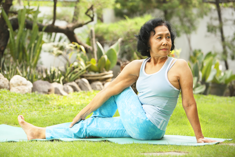 Older lady doing yoga in a park