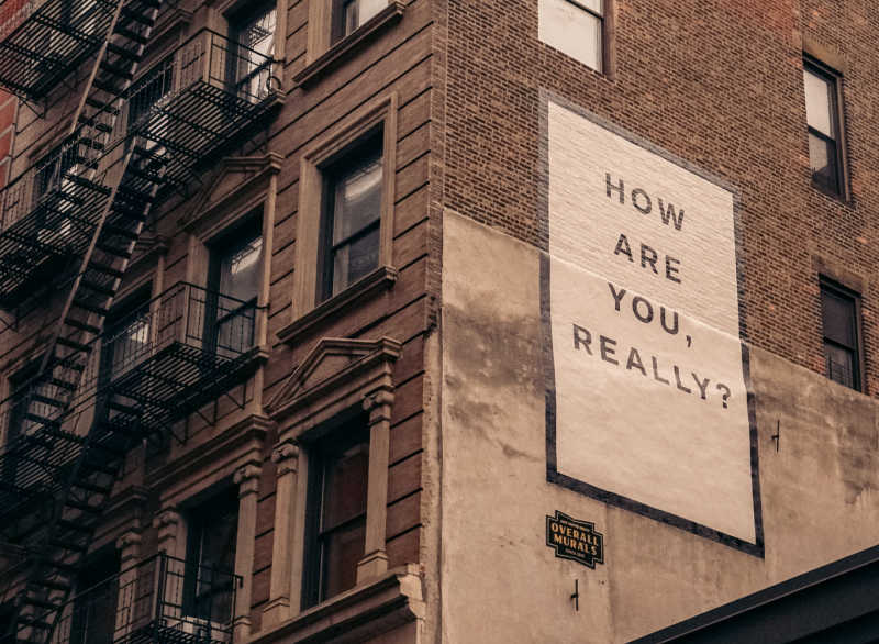 Large mural saying 'How are you really' on side of brownstone building