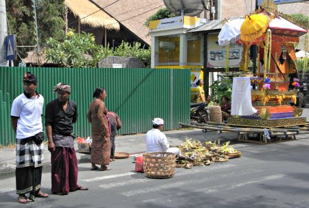 Balinese sitting in the street preparing for a cremation