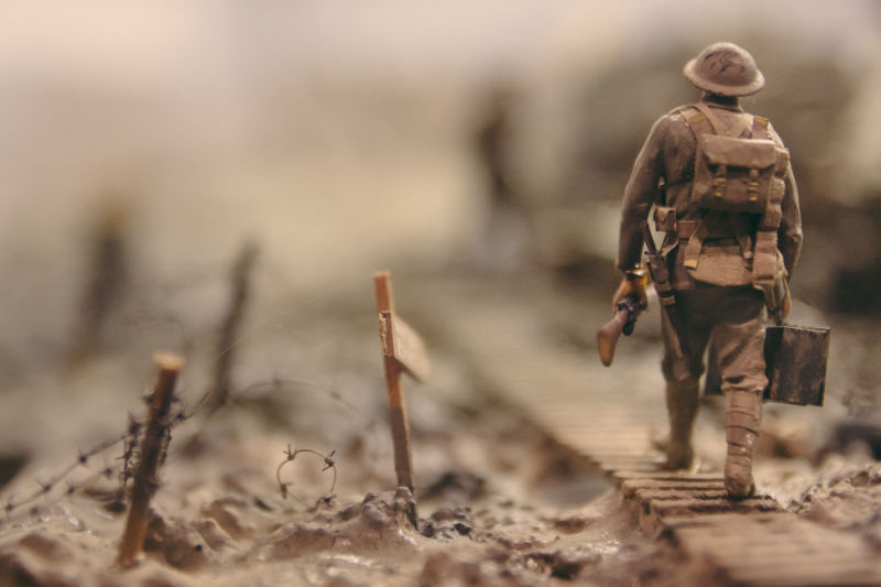 Soldier walking past barbed wire. Photo by Stijn Swinnen at Unsplash