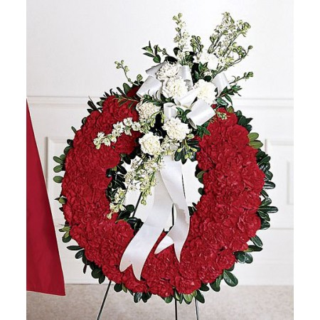 Military funeral flowers, a circular red wreath with crest.