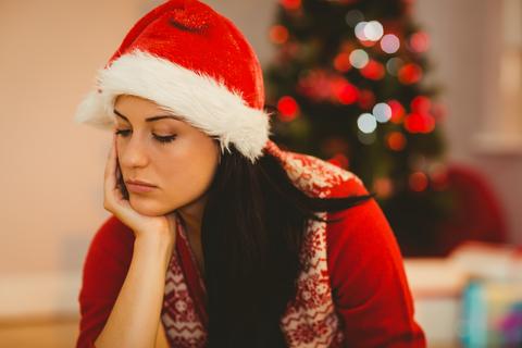 woman feeling grief at xmas wearing a santa hat