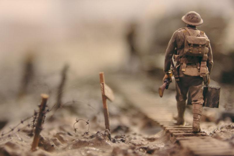 Soldier walking past barbed wire. Photo by Stijn Swinnen at Unsplash