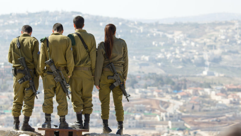 Four soldiers overlooking city. Photo by Timon Studler at Unsplash